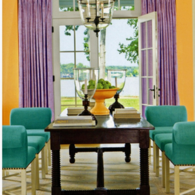 The light orange walls, purple drapes and the turquoise chair around the table come together to create a split complementary room.