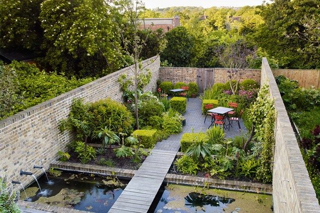 Walled garden with an unusual water feature, outdoor table and seating area.