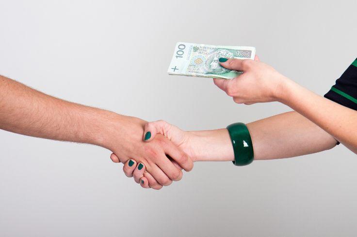 osoba przekazująca drugiej osobie plik banknotów stuzłotowych