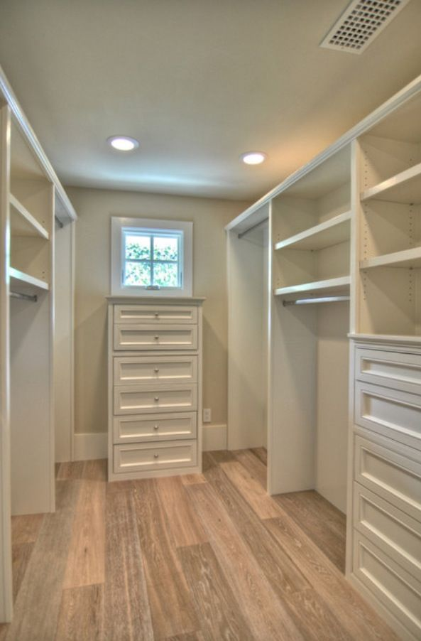 "The Ultimate Walk-in Wardrobe: Mirrored Doors, Small Lounge-Chair & Plush Rug, Make-up Vanity with Mirror, Freestanding ""Island"" Storage, Small Window or Sky-Light"