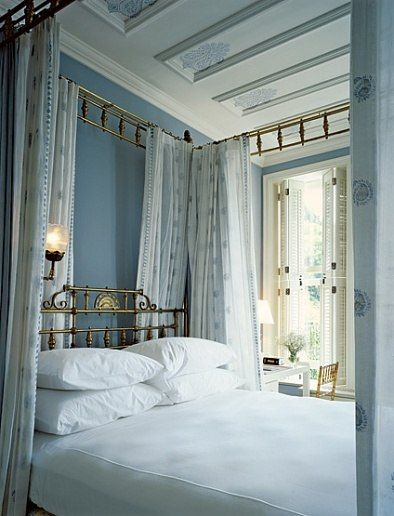 By Mica Ertegun. Beautiful antique brass four-poster bed with blue and white