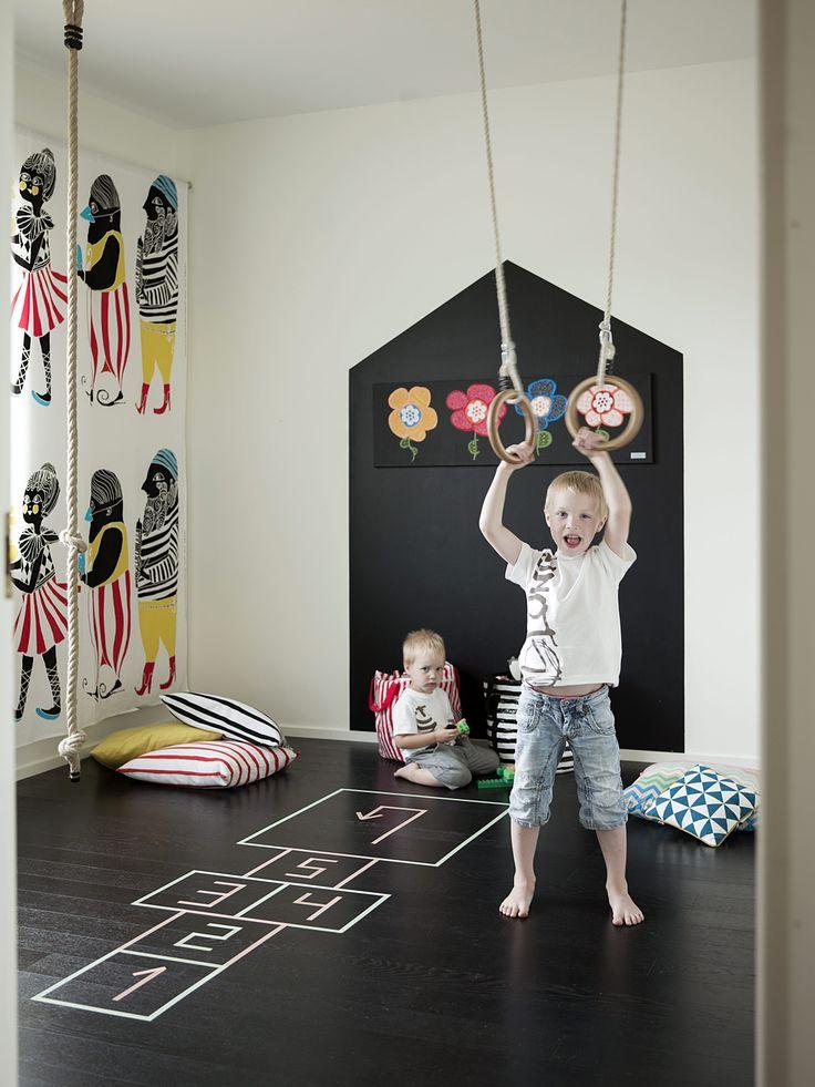 Lastenhuoneen mustaksi maalattuun lattiaan voi teipata erilaisia hyppyruudukoita ja pelejä. Kiipeilyköysi ja temppurenkaat kehittävät motoriikkaa ja ovat aina valmiina leikkeihin, kun ne roikkuvat esillä. Väritys on poimittu Maija Louekarin Marimekolle suunnittelemasta Kulkue-kankaasta.