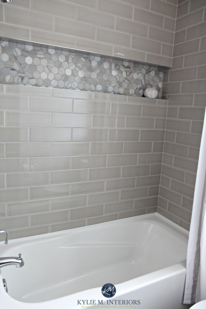 Bathroom with bathtub and gray subway tile shower surround with niche or alcove in hexagon marble tile, greige accent tile. Kylie M Interiors design