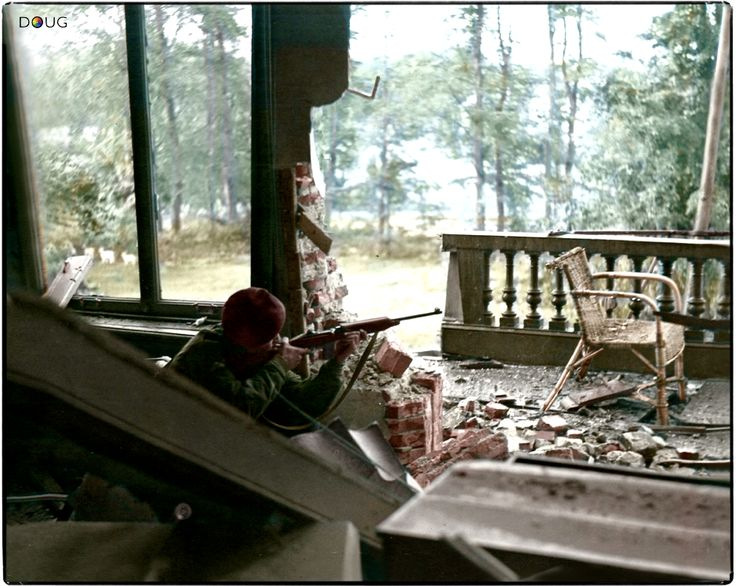 British Paratrooper taking aim with an American M1 carbine from the first floor balcony of the Hartenstein Hotel in Oosterbeek, near Arnhem in The Netherlands. September 1944.