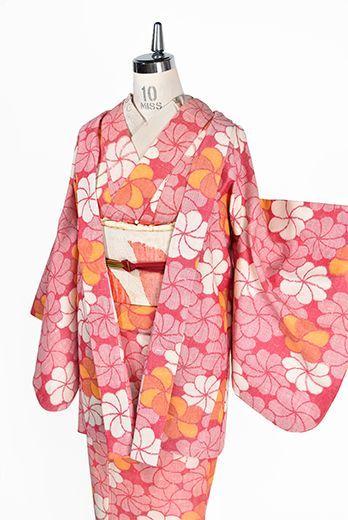 ポピーレッドとオレンジのバイカラーでデザインされた一面のねじり花文様が愛らしいウールのアンサンブル(着物と羽織のセット)です。