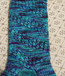 This is a toe up lace sock in 3 sizes. Small (60 stitch leg), Medium (66 stitch leg) & Large (72 stitch leg). There is an option for doing the toe in an eye of partridge stitch. The stitch pattern is charted and written out.