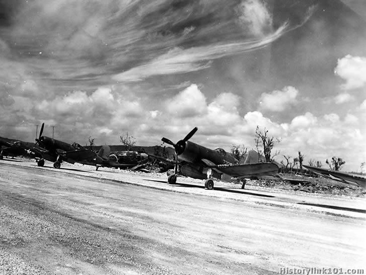 On the new Orote airfield on Guam, Marine Corsairs, manning the recently captured strip, provide a strange contrast to the battered Jap Mitsuibishi bomber in the background. The bomber was one of 76 Japanese planes captured by invading Marine troops which wrested the airfield from Japanese hands on July 29 after weeks of naval shelling, aerial bombardment and artillery barrages of the coral airdrome. August 8, 1944