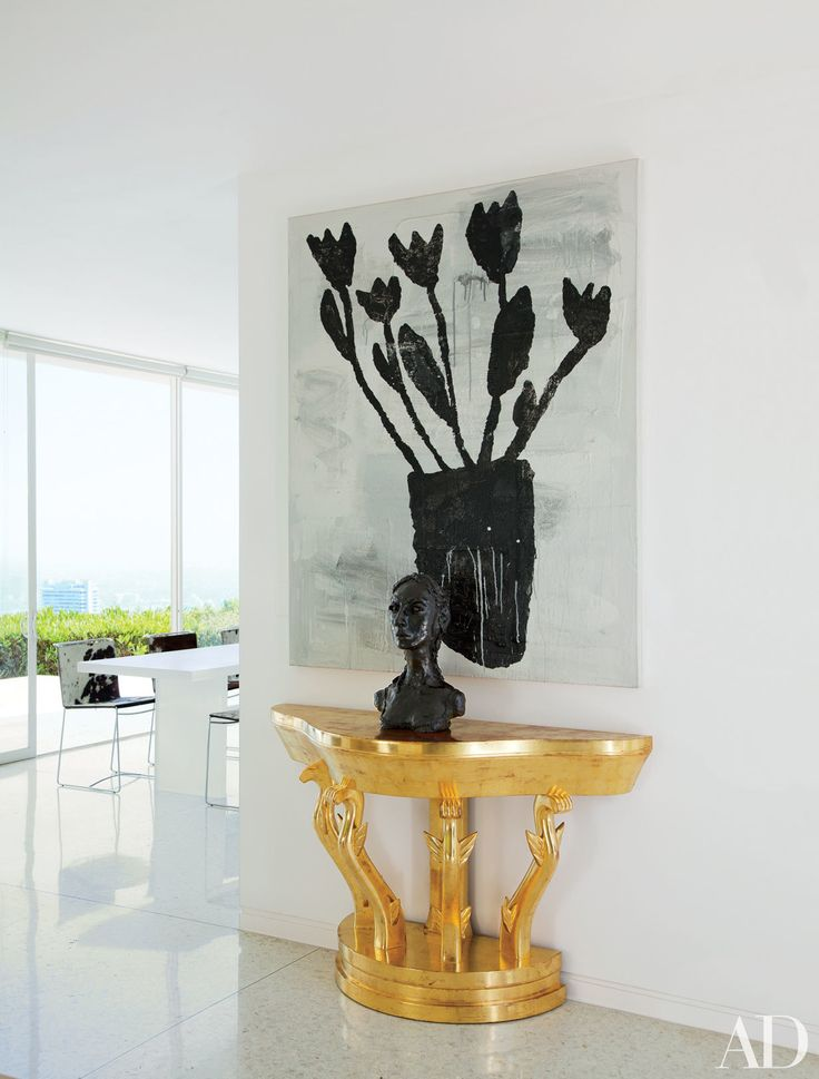The contrast, white modern interior with a graphic painting by Donald Baechler, bronze bust by Anh Duong & a vintage gilded console // Designer Donald Romualdez' LA home