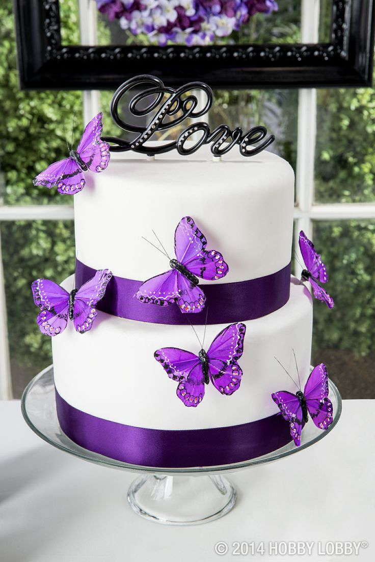 This white and purple wedding cake with purple butterflies