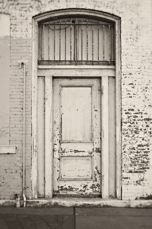 Peeling white paint of a door and brick wall