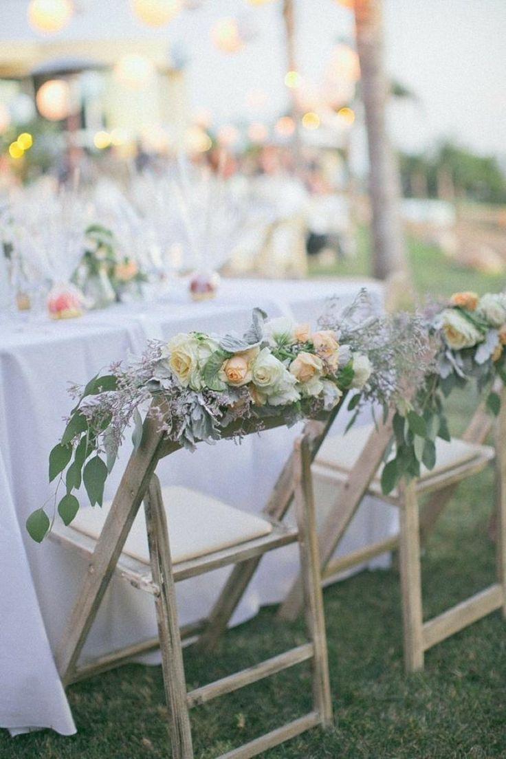 déco mariage champêtre - chaises en bois grisâtre décorées de guirlandes de roses et feuilles