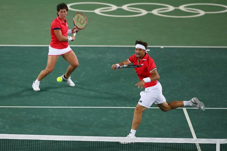 RIO DE JANEIRO, BRAZIL - AUGUST 11: David Ferrer of Spain (R) and Carla Suarez Navarro of Spain in action during the mixed doubles first round match against Andy Murray of Great Britain and Heather Watson of Great Britain on Day 6 of the 2016 Rio Olympics at the Olympic Tennis Centre on August 11, 2016 in Rio de Janeiro, Brazil. (Photo by Clive Brunskill/Getty Images)