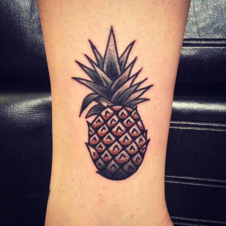 Traditional style pineapple tattoo on the left foot, above the inner ankle bone.