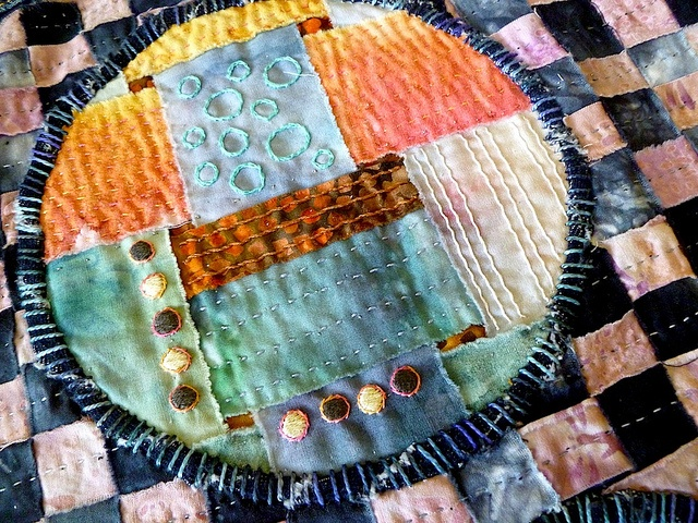 Crop circles Textile detail. Two woven cloth pieces, cut and interchanged (with a third, not shown here). Fabrics are a combination of commercial batiks, and hand dyed and hand painted cottons. Embroidered details, and hand quilted with variegated size 12 quilting cotton and cotton embroidery floss.