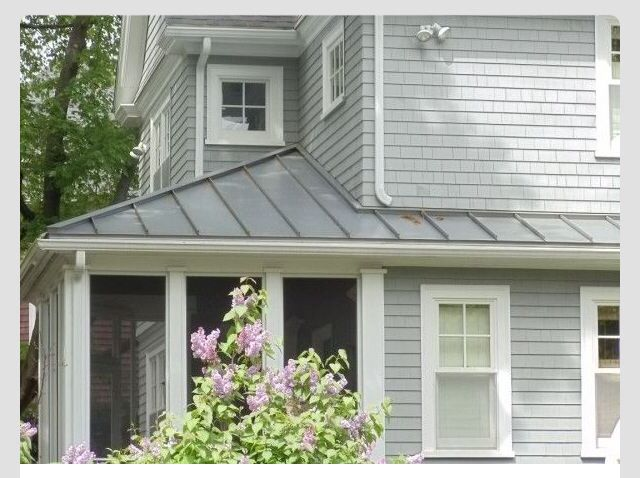 Light grey house, charcoal metal roof, white trim.