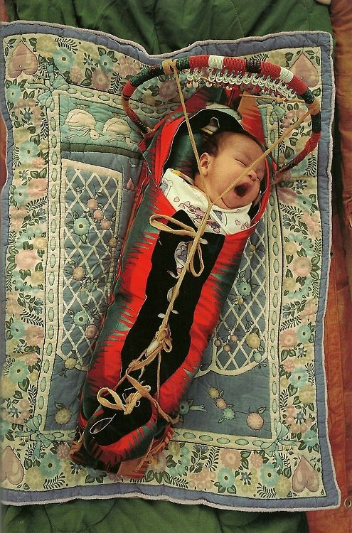 Native American baby in a cradle board at the annual powwow in White Swan, Washington. National Geographic | June 1994