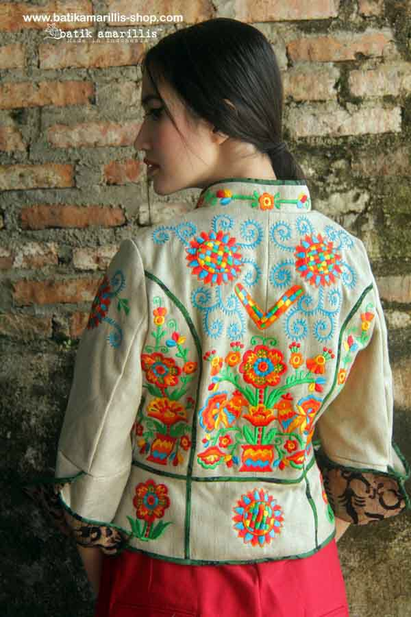 Batik Amarillis's Ryder Jacket in classic Hungarian embroidery beautiful assymetrical design part of riding & part of military inspired jacket, features criss cross batik piping & lining. You can change the look by playing with the front button and the front flap of the jacket!