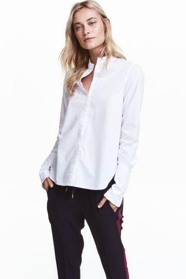 Хлопковая блузка с оборками: Прямая блузка из хлопковой ткани. На блузке низкий воротник стойка с оборками, а также потайная застежка спереди. Оборки вдоль планки. Широкие подогнутые манжеты на пуговице с оборками. Спинка немного удлиннена.