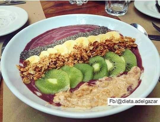 Smoothie con base de Açai, uva y banano con leche de almendras. Encima tiene banano y kiwi,  De toppings: Mantequilla De Maní Suna , semillas de Chía y GranolaSuna  Por ejemplo de otreas opciones pueden ponerle: semillas de chía, granolitas, avena, kiwi, banano, fresas, goji berries, mantequilla de maní SUNA, granola, coco, almendras tostadas, marañones, entre muchos más.