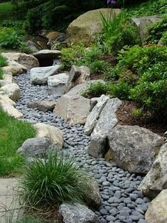 Dry creek bed edges the bottom of a planted hill -