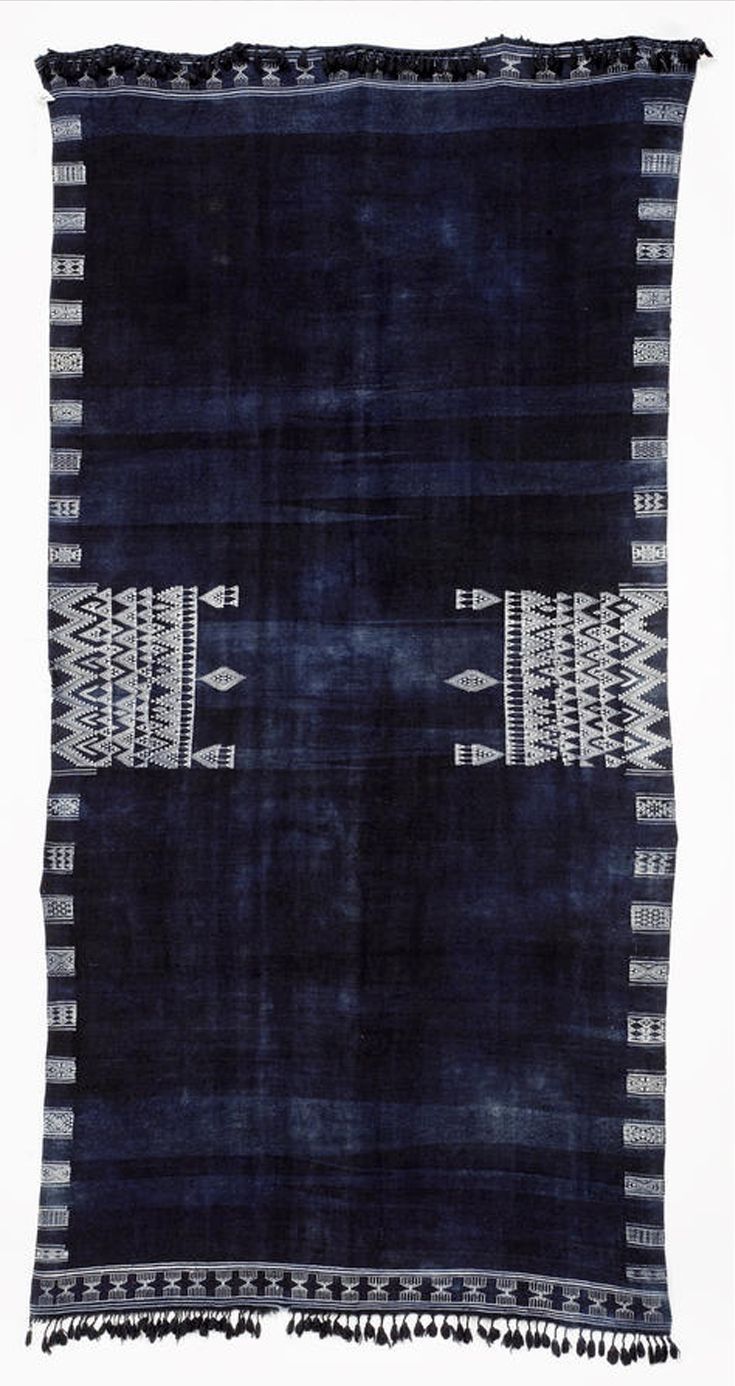 Africa | A shawl, Bakhnuq, from Tunisia | Wool  cotton; the indigo field with two central rectangular panels of white zig-zag and pendant motifs, with geometric borders, tassel fringes to either end