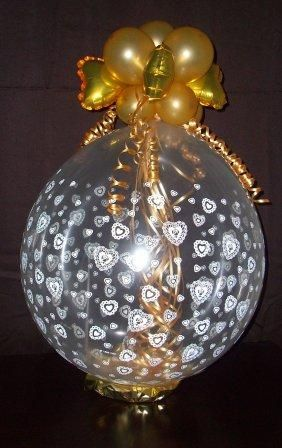 Golden Hearts and Tendrils-  A perfect focal-point for weddings and anniversaries, this features a gold balloon collar with heart foils atop a heart-printed balloon and flowing golden ribbon tendrils inside. This creation sets the tone for an elegant event. Add a bottle of sparkling wine to this composition.