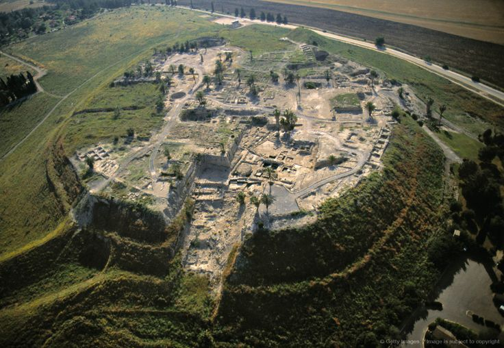 """Megiddo is a tell (mound) in northern Israel known for its historical, geographical, & theological importance, especially under its Greek name Armageddon. Megiddo is strategically located at the head of a pass through the Carmel Ridge overlooking the Jezreel Valley from the west. The Book of Revelation mentions an apocalyptic military amassment at Armageddon, a name derived from the Hebrew """"Har Megiddo"""" meaning """"Mount of Megiddo"""". 'Armageddon' has become a byword for the end of the age."""