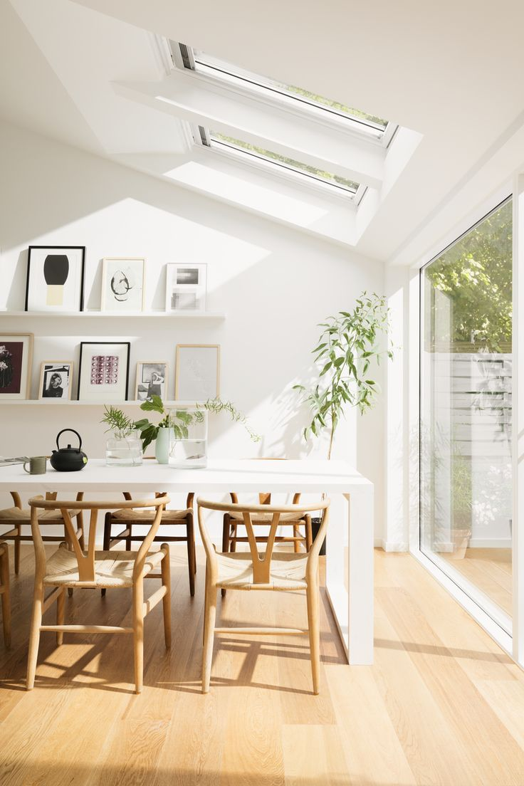Roof windows and increased natural light. These stunning roof windows by VELUX® can transform a home. Dining room with white roof windows.