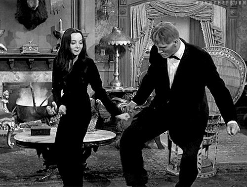 Morticia Addams trying to teach Lurch to dance.