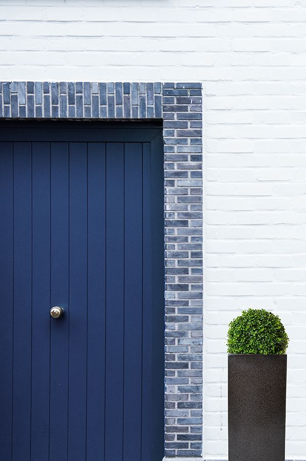 Artificial Buxus Ball in Tall Black Planter next to blue front door. Front Door Styling. Home Exterior.