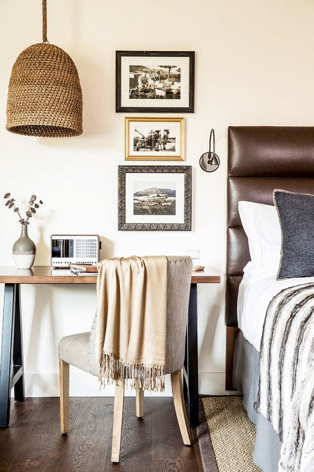 Warm colored bedroom with leather brown headboard, home desk station and wicker lamp