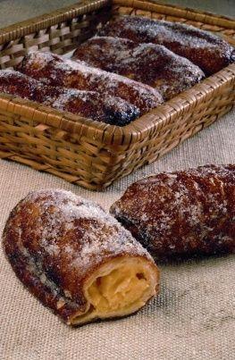 Postres: Xuixo de Girona, gastronomia catalana. El suso (a veces también chucho o susú, del catalán xuixo o xuxo) es un pastel dulce típico de Gerona (Cataluña, España) consistente en una masa fina de forma cilíndrica rellena de crema, frita y azucarada por fuera.