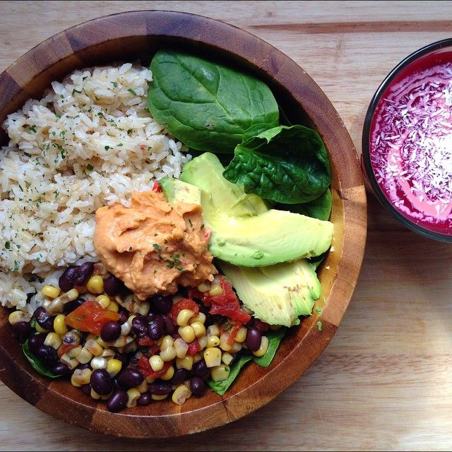 Mexican inspired salad bowl for lunch!! brown rice, black bean corn salsa, avocado and hummus on a bed of spinach with a berry smoothie topped with unsweetened dried coconut