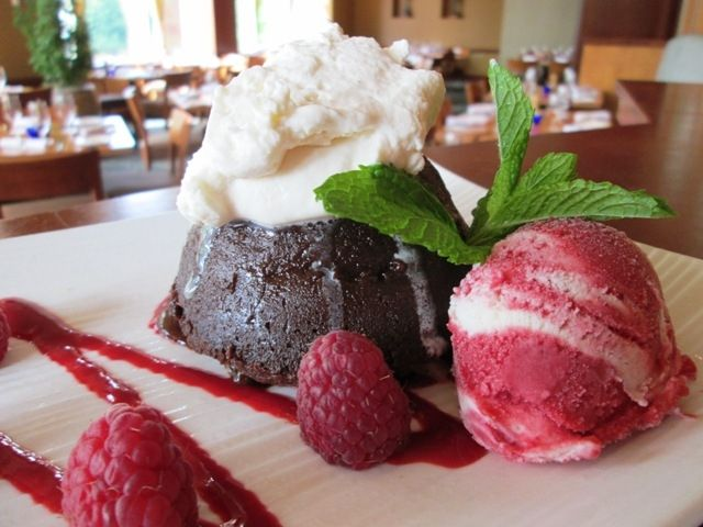 Rich warm Chambord dark chocolate cake with raspberry coulis, vanilla whipped cream and a raspberry-vanilla swirl of sorbet and ice cream. #seastar #dessert #chocolate #moltencake #bellevue