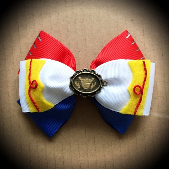 Toy Story Character Inspired Jessie Disney Pixar Cowgirl Hair Bow  Red Blue and White Grosgrain Ribbon Decorated with Felt Accents and Belt buckle centrepiece.  Mounted on an alligator clip.  I can do custom bows, just let me know if youd like something specific.  Price is for single bow.