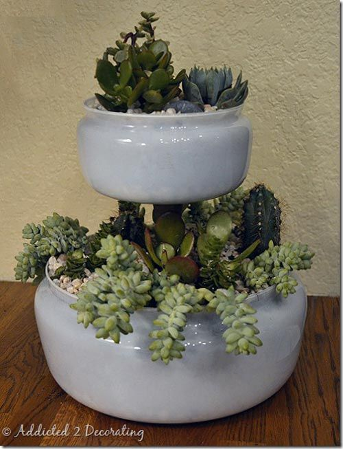 """Inexpensive Two-Tiered Tabletop Planter """"In case you couldn't tell, the bones of this project are actually glass light covers in two different sizes plus one wood candlestick holder. Throw in an adhesive of your choice, and that's about all it takes. Then you can get crafty adding the soil and plants of your liking."""""""