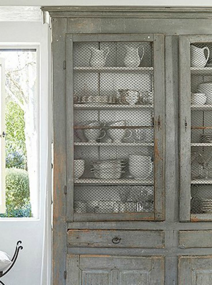 Beautiful French antique country cupboard with chicken wire and white dishes on shelves