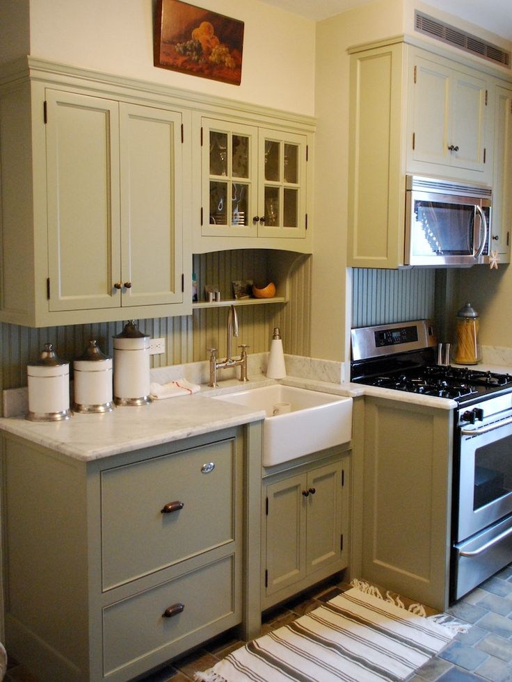 Farmhouse kitchen in sage green by Hudson Cabinetry.