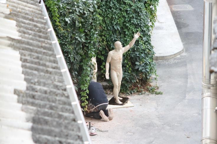 El escultor Arturo Nogueira trabajando en la puerta de su estudio de Villafranca del Bierzo desde una ventana de nuestra posada