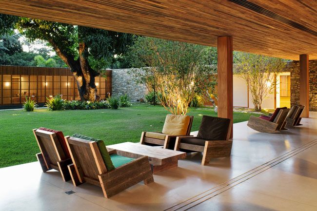 Bahia House  Studio MK27  Salvador, Brazil  The house was designed so that living and dining areas open onto a grassy courtyard where two existing mango trees thrive. The Asturias armchairs of recycled wood were designed by Carlos Motta.  Photo © Nelson Kon
