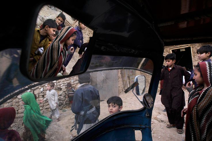 Children, seen from inside a rickshaw, gathering in a slum on the outskirts of Islamabad.
