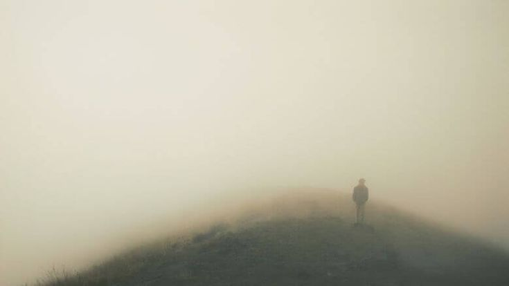 man-standing-on-hill-in-fog