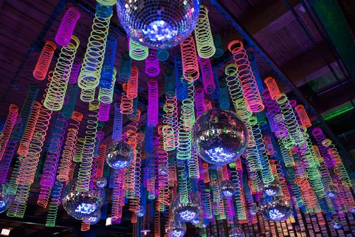 The custom installation combined glittering disco balls with glow-in-the-dark toys.