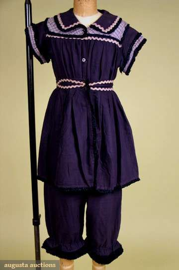 """Lady's wool bathing suit costume, English, c1904;  piece soft blue-black wool twill: short sleeve button front """"suit"""", blue and white cotton plaid insertions, white rick-rack, silk fringed ribbon trim on collar, sleeves and leg hems, short button on overskirt, B 44"""", W 26"""", L 43.5"""", Skirt L 16"""""""