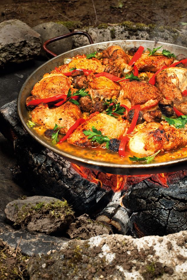 Beyond S'mores. Four top chefs share the secrets of great campfire cuisine like this chicken and chorizo paella simmering over the campfire!