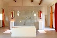 Au centre de la pièce trône, magistrale et impromptue, la salle de bains. Habillée de parois en verre et du même carrelage qu'au sol, elle se