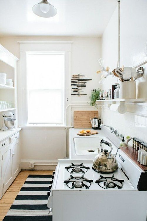 small apartment kitchen. Nicely organized, knives, shelf over sink and stove...