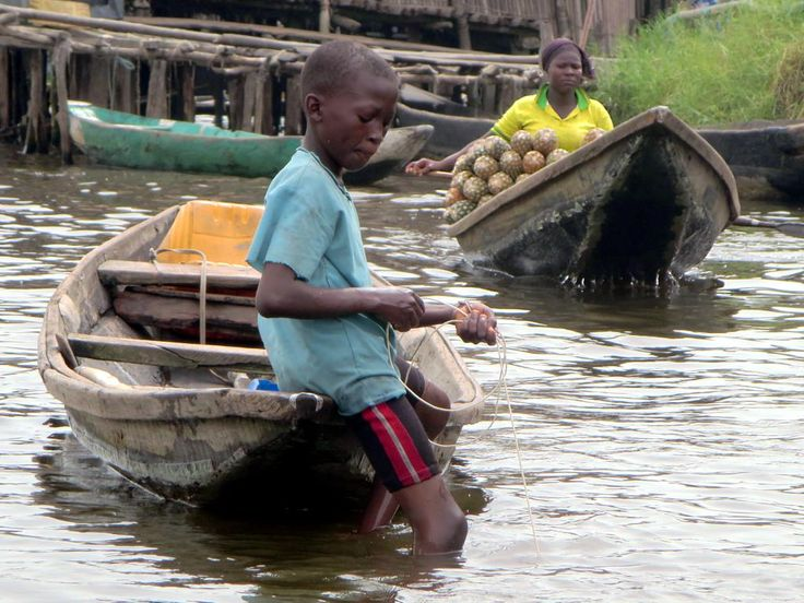 A woman with a canoe load of pineapples sets out at Ganvie village on Lake Nokoue near Cotonou, Benin.