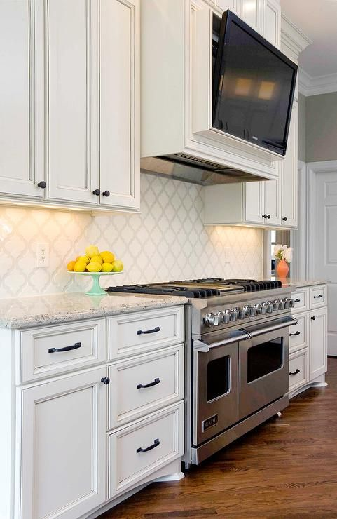 Lovely kitchen features ivory cabinets adorned with oil rubbed bronze hardware paired with white and gray granite ocuntertops and a Mission Stone Tiles Beveled Arabesque Tile backsplash.