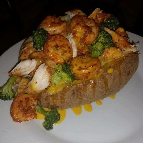 Overloaded baked potato with chicken, shrimp, broccoli, and cheese